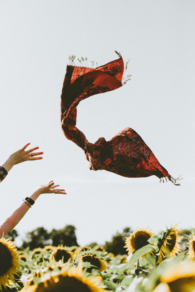 Woman letting go of scarf in a field of sunflowers. Importance of living an uncluttered life.